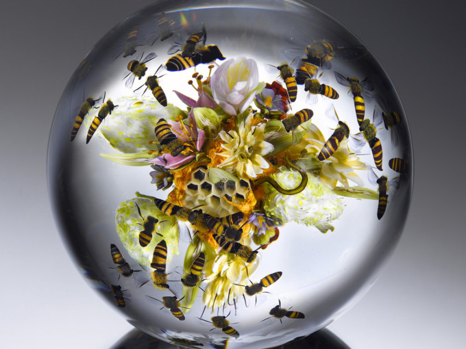 A paperweight by Paul Stankard featuring a flower and fruit bouquet with swarming honeybees