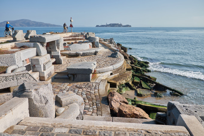 The Wave Organ, an assembled concrete structure on a jetty in san francisco overlooking San Francisco bay and Alcatraz island in the background.