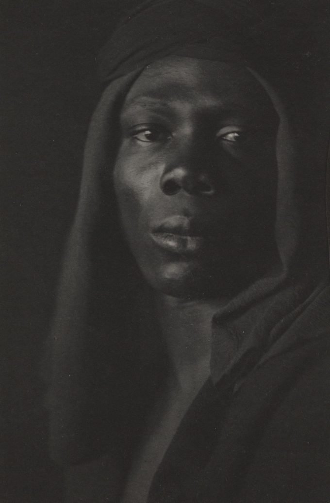 A platinum print by Fred Holland Day called Ebony. A portrait of an black male with head covering.