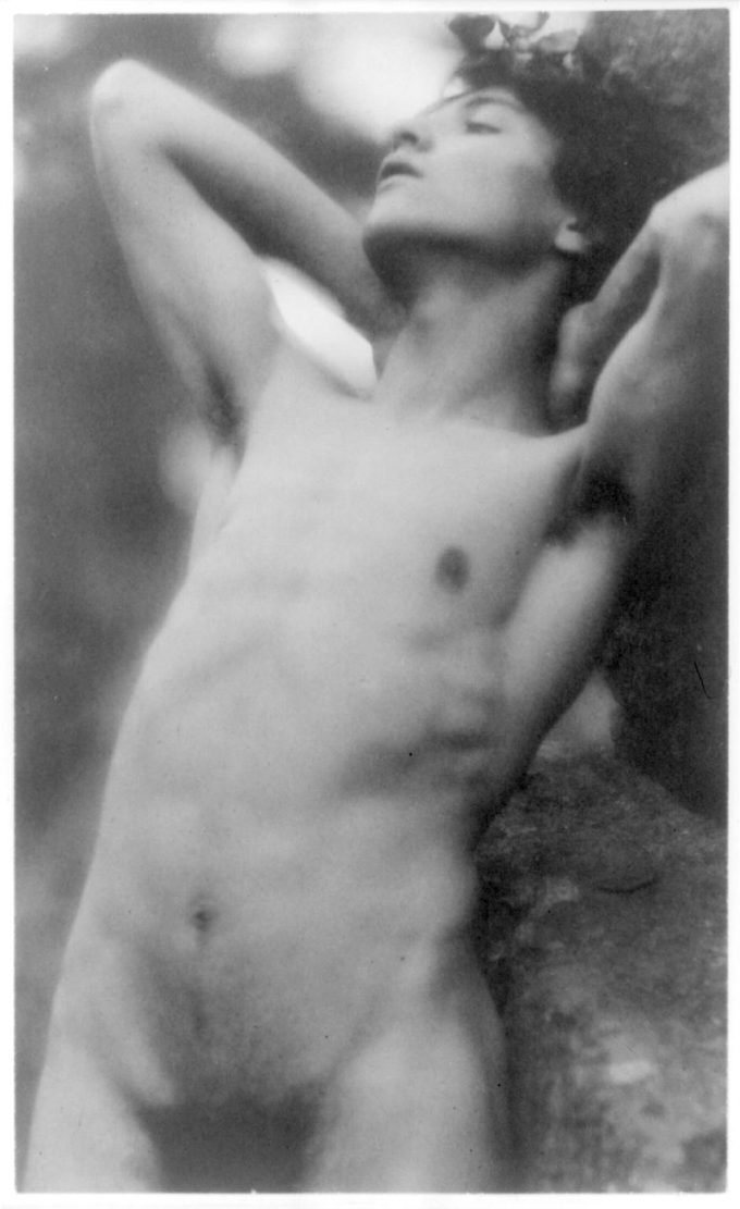 Platinum print by Fred Holland Day. Depicting a nude youth with laurel wreath against rock with hands behind neck, cropped at thighs