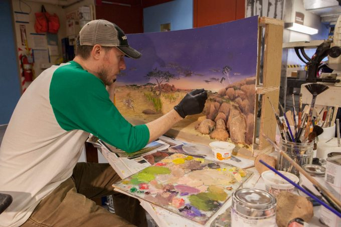 Field Museum staff artist Aaron Delehanty paints a minature of striped hyena diorama backdrop