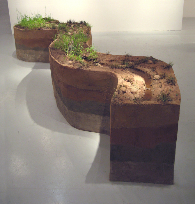 """Running Stream"" is inspired by a stream in rural Maryland; the soil, rocks and live plants in this piece are taken directly from that site. Alternating displaced natural sections from the site and sections recreated in concrete with artificial foliage, complete the continually flowing 20' long sculpture."