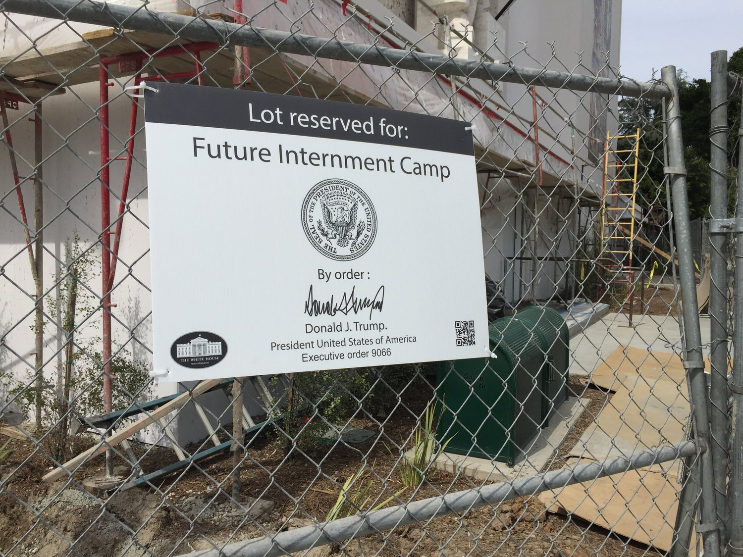 Construction site fence with a large official looking sign declaring the sight reserved as the location of a future internment camp.