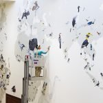 Artist Jane Kim working on the wall of birds mural