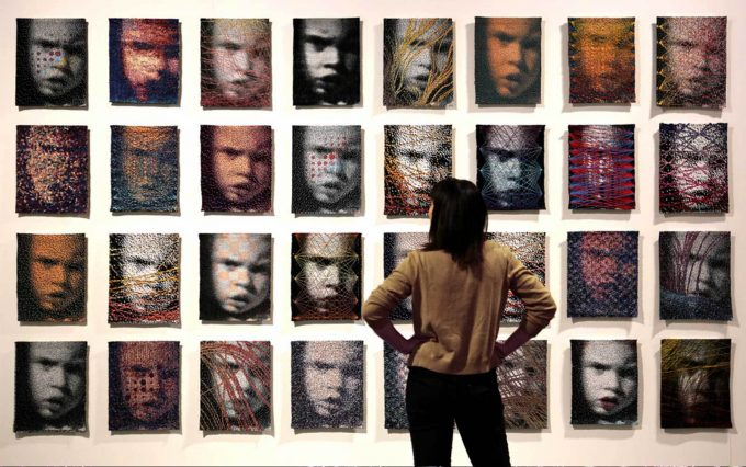 An instilation of woven portraits, each woven differently, of a young girls face hung on a wall.